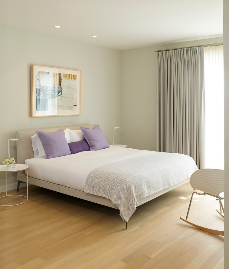light purple pillows artwork beige bed headboard white bedding white side tables grey curtains table lamps white pillows grey walls wooden floor chair