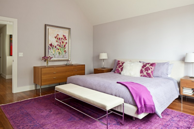 light purple pillows purple bedding purple area rug wooden nightstands and console white table lamps purple walls white bench white shag pillows wooden floor