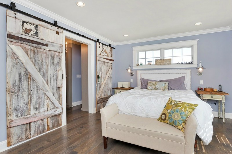 light purple pillows purple walls white bed white bedding bench barn door black hardware windows wooden side tables industrial wall sconces wooden floor