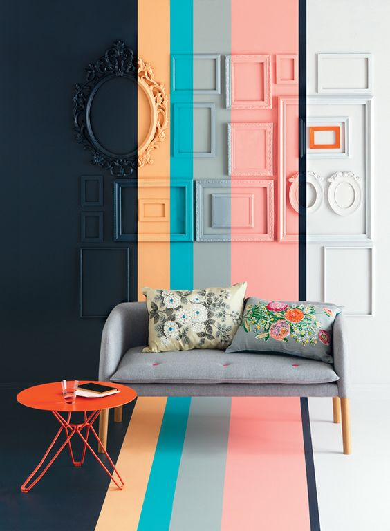 living room with black, orange, blue, grey, pink, white painted wall, grey sofa, orange coffee table