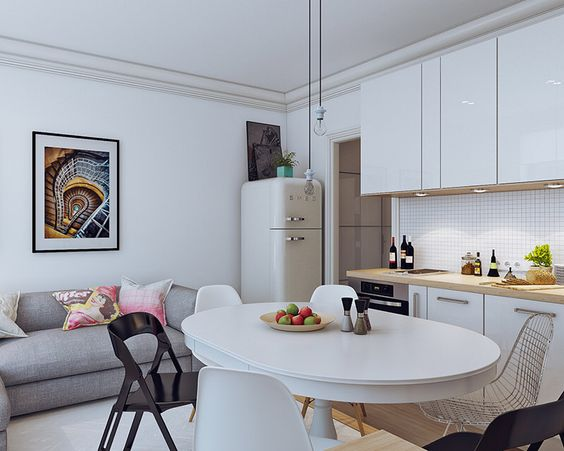open kitchen with white kitchen cabinet and brown top counter, round white dining set with white and black shairs, grey sofa