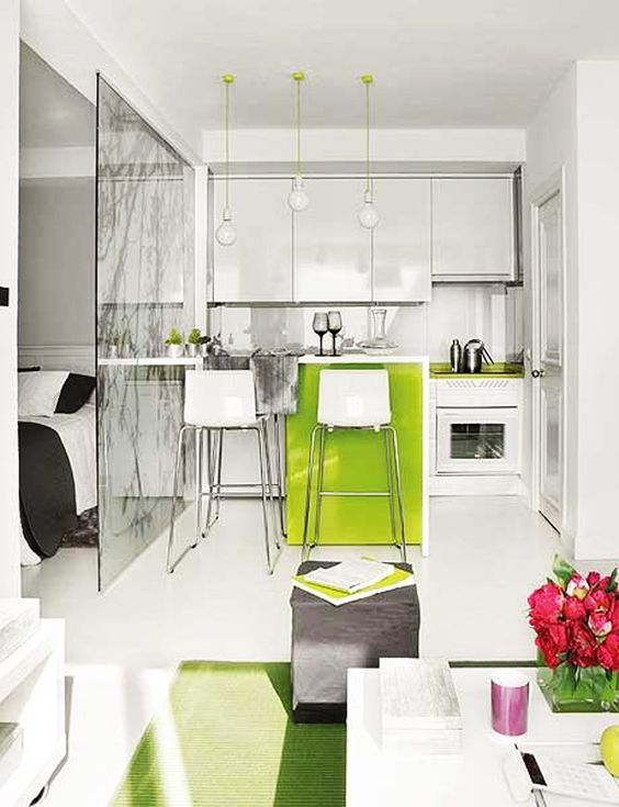 open space with white kitchen with neon green cabinet, green top counter, living room with white coffee table, bedroom