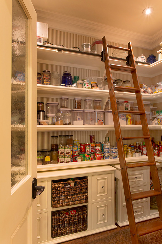 pantry ladder beige wooden shelves wooden drawers rattan baskets wooden ladder black iron railing wooden floor glass jars frosted glass door