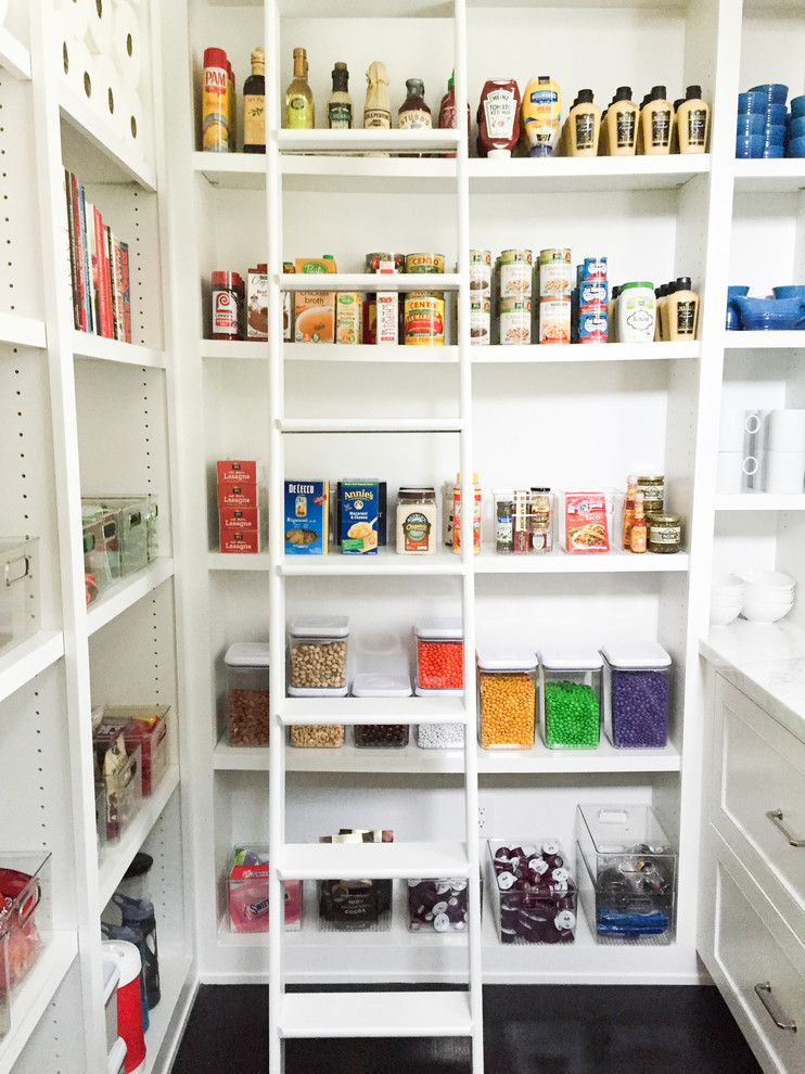 pantry ladder white walls white shelves glass storage jars cans black flooring white wooden ladder white drawers white cups glass baskets