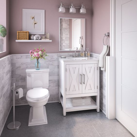 small bathroom with grey tiles, pink painted wall, white cabinet, white toilet, off white tiles