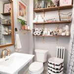 Small Bathroom With Polkadot Tiles, White Painted Wall, Brown Wooden Shelves On Top Of White Toilet And Laundry Bag, White Sink, Golden Framed Mirror