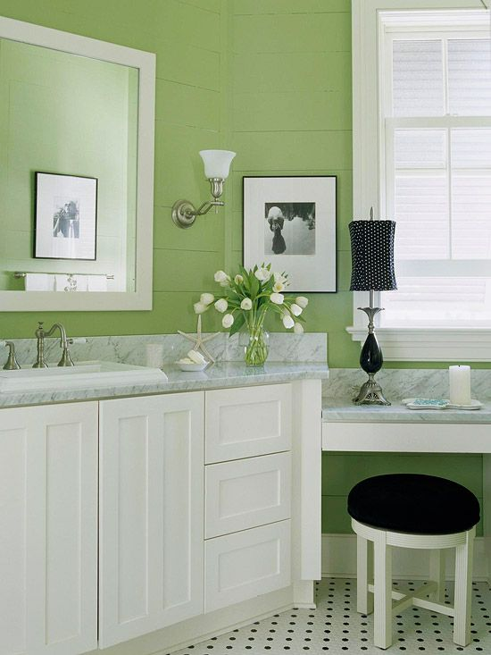 small bathroom with soft light green painted wall. white cabinet, grey top, white wooden stool with black cushion, mirror, black table lamp