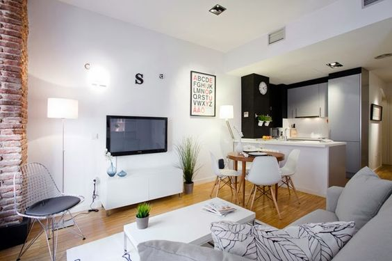 small kitchen with small round dining set all in white, white rug in living room, grey sofa, white coffee table