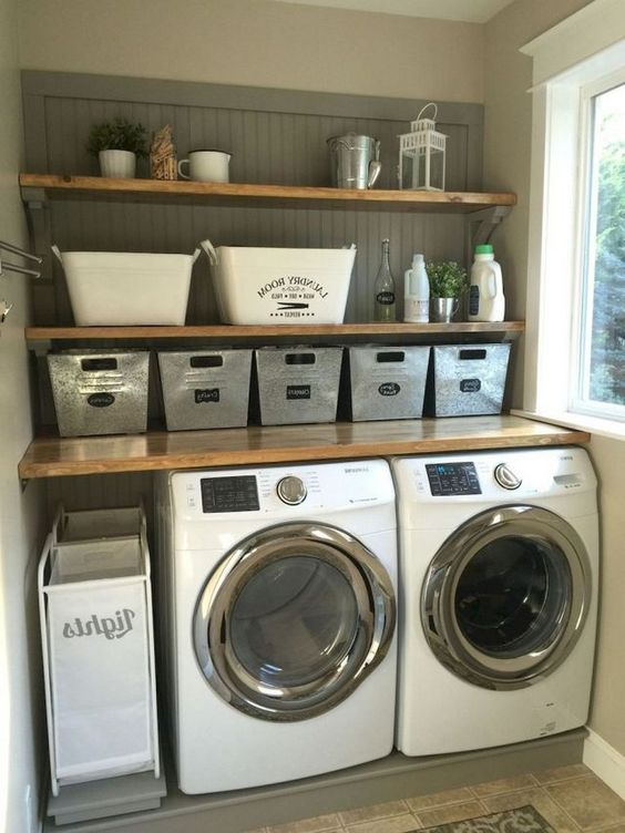 small laundry room with brown wall, brown wooden shelves, two machines, metal laundry basket