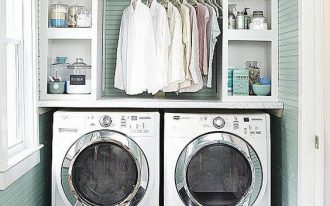 small laundry room with green wooden wall, two machines, shelves on top for cleansing liquid, detergent, baskets, and clean clother