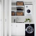 Small Laundry Space With Black Machine, White Cabinete With White Marble Top, White Wooden Shelves, Baskets, White Machine