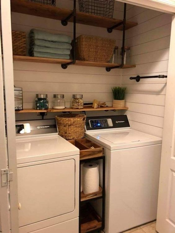 small laundry space with white wooden walls, shelves between two machines, shelves on top, sliding door