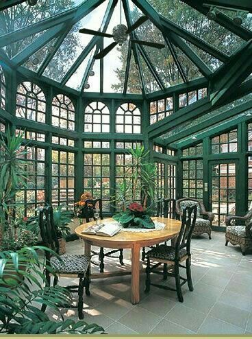 sunroom with green painted framed of windows, ceiling, plants, round dining table and chairs, ceiling fan