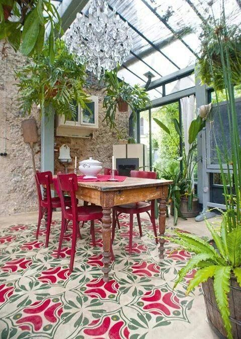 sunroom with hanging plants, crystal chandelier, wooden table, pink wooden chairs, pink green patterened tiles