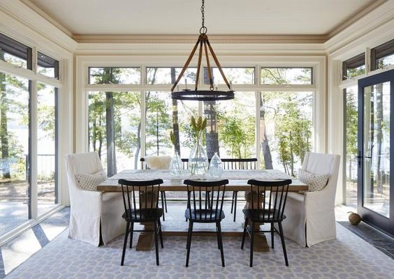sunroom with tiles floor, white ceiling, clear glass windows wall, thin chandelier, wooden table, sofa and chairs