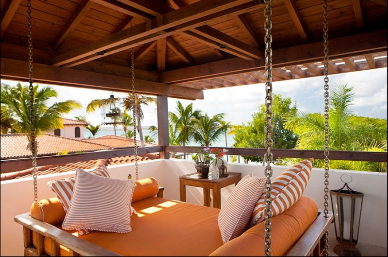 swing hammock bed chains rope wooden bed light fixture wooden beams wooden ceiling orange cushion striped black and white pillows wooden side table glass top