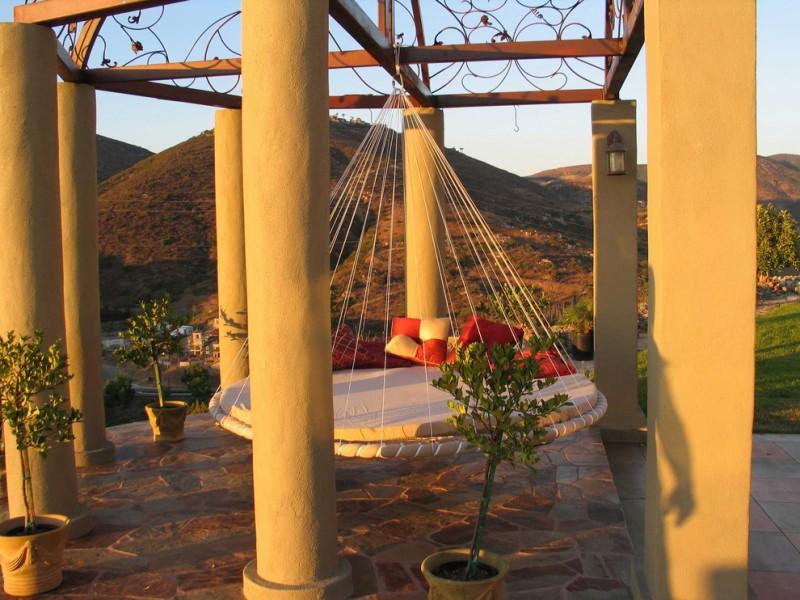 swing hammock bed hammoc rope big outdoor pillars brown flooring red pillows white round hammoc cushion open ceiling