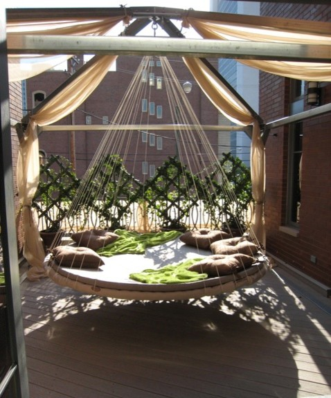 swing hammock bed white rope round hammock bed wooden flooring open space red brick walls black glass window green throw brown pillows cream drapes