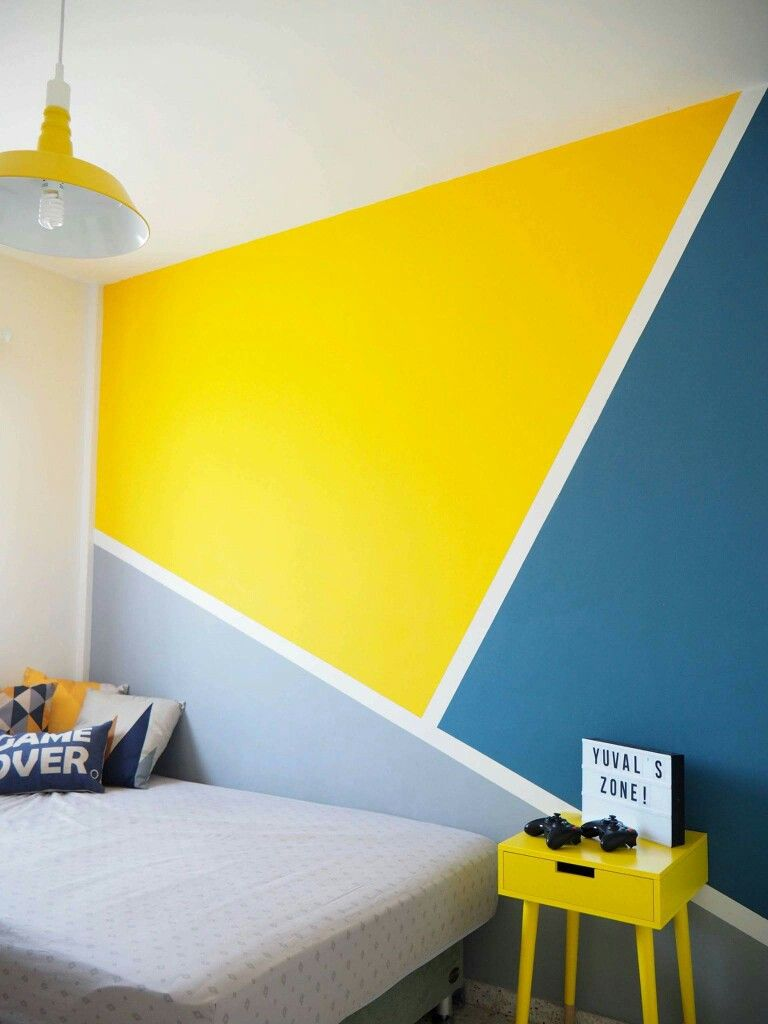 a bed room with white walls and ceiling, accent wall with yellow, blue, and grey paints, yellow side bed, grey bed
