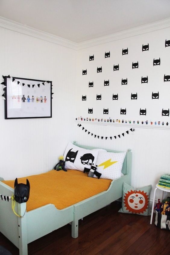 a bedroom with blue bed, yellow linene, batman pillows, batman masks wallpaper, wall picture with superheros, action figures