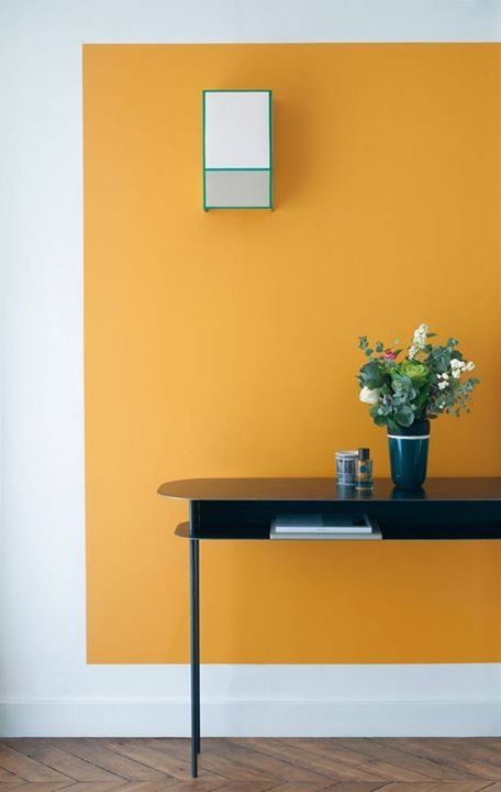 a big area of orange on the wall with white surrounding wall, a black table, a mirror