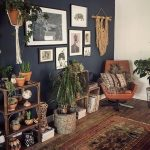 A Coner With Wooden Floor, Rug, Brown Leather Chair, Plants On The Shelves, Macrame, Pictures On The Wall, Book Shelves