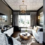 A Living Room With Wooden Floor, White Sofa, Animal Print Chair, Animal Print Rug, Dark Grey Wall, Artistic Chandelier, Round Coffee Table, Patterned Ceiling