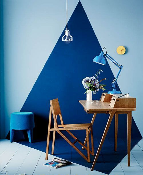 a room with dark blue rectangular shape on the center of the room in floor and wall, light blue on the surrounding, wooden table and chair, blue tale lamp, yellow clock