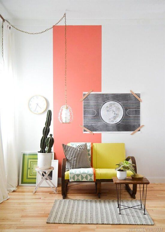 a room with orange thick line on a certain part of the white wall with wall picture, plants, yellow sofa, rug, coffee table