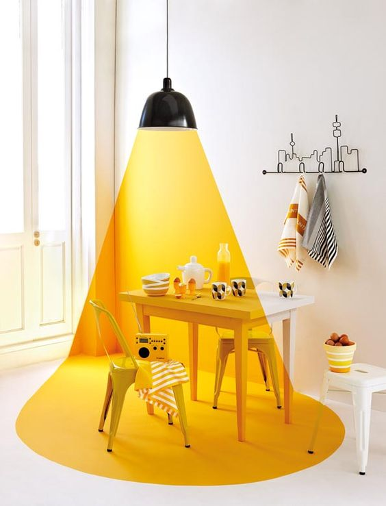 a room with yellow paint on the wall and floor to create illuminated effect on the white room, the effect is on the furniture also