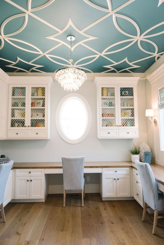a study room with wooden floor, white wall, patterned blue ceiling with chandelier, white cabinet with wooden table top, chairs, white cupboards