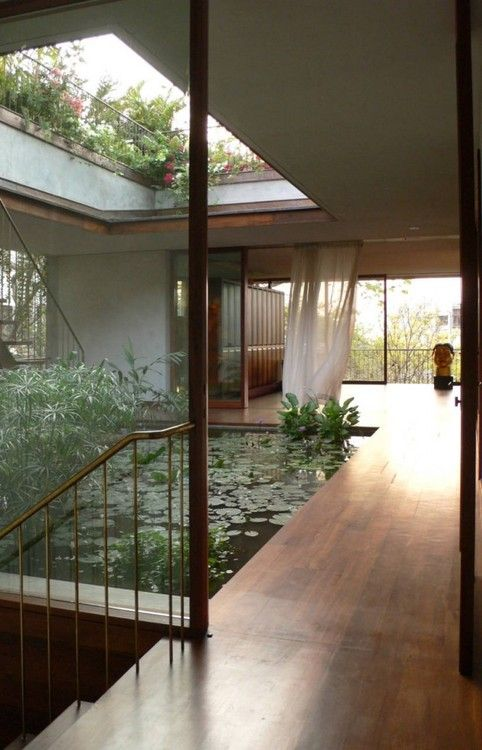 amedium sized pond with water plants surrounded with wooden floor, with open ceiling, plants and rail