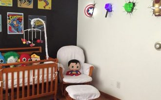 baby room with superman purple rug, white chair with ottoman, superman doll, superheroes doll on the crib, wall poester, wall decors