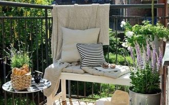 balcony with brown wooden floor, white wooden bench, round small side table, plants on the silver pots on the floor, rug