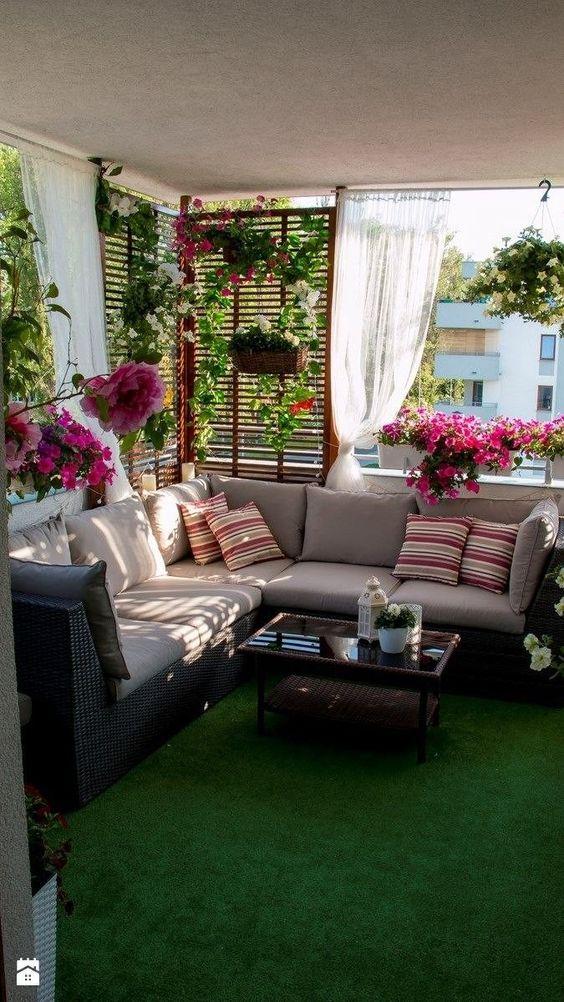balcony with green floor, grey sofa, flowers, plants, wooden shade, curtain