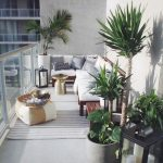 Balcony With Grey Floor, Grey Wall, Wooden Bench On The Corner, Golden Side Table, Ottoman, Plants