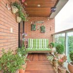 Balcony With Wooden Floor, Open Brick Wall, Plants On Pots On The Floor, On Floating Pots On The Wall, Wooden Chair With Green Cushion