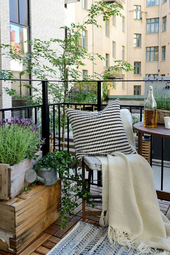 balcony with wooden floor, rug, wooden chairs and table, plants on wooden pots