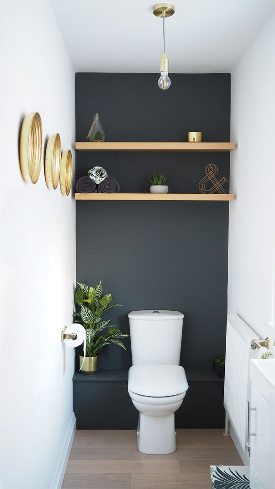 bathroo with white ceiling, walls, dark grey accent walls, white oitlet, golden shelves, golden wall accessories, wooden floor