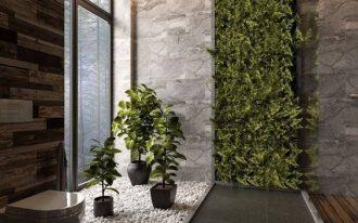 bathroom big grey tiles floor, white toilet, white stones with pots of plants, plants on the grey walls, wooden walls, wooden floor on shower area
