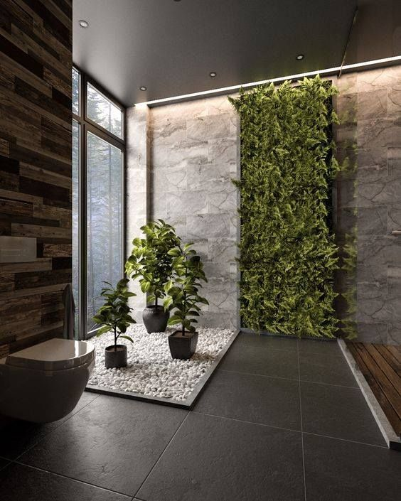 bathroom big grey tiles floor, white toilet, white stones with pots of plants, plants on the grey walls, wooden walls, wooden floor on shower area