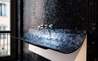 bathroom black mosaic tiles on floor, wall, on curving forward wash basin, silver faucet