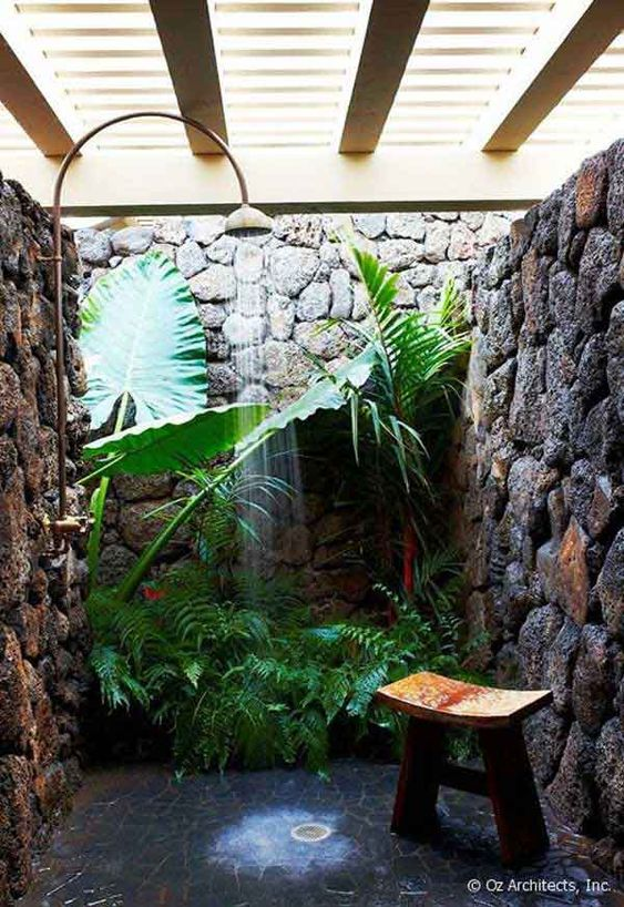 bathroom black stones floor, black stones wall, plants, light wooden pergola, shower, plants on the corner