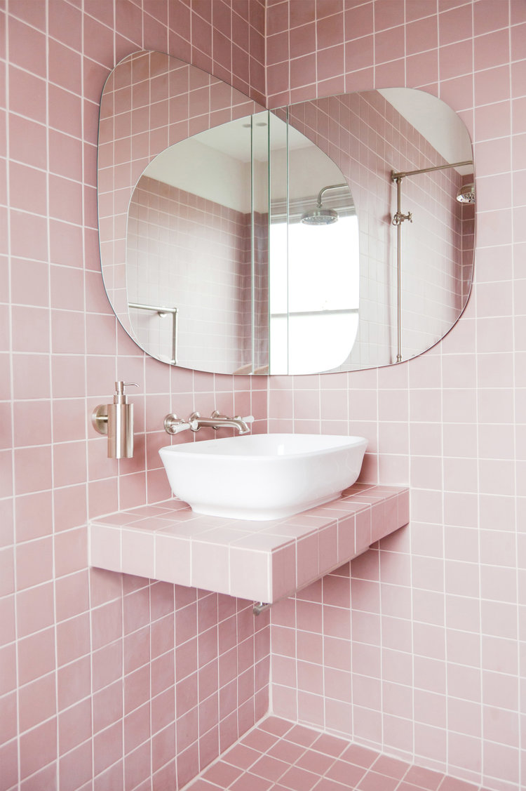 bathroom canity with pink square tiles on the entire wall, white sink on pink tiles on vanity, corner mirror