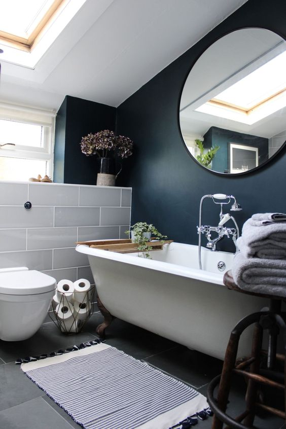 bathroom, grey floor tiles, black wall, white tub, round mirror, white toilet, white partition tiles