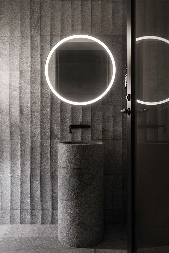 bathroom vanity with grey floor, grey jagged wall, grey stone barrel sink with black faucet, round mirror with light frame
