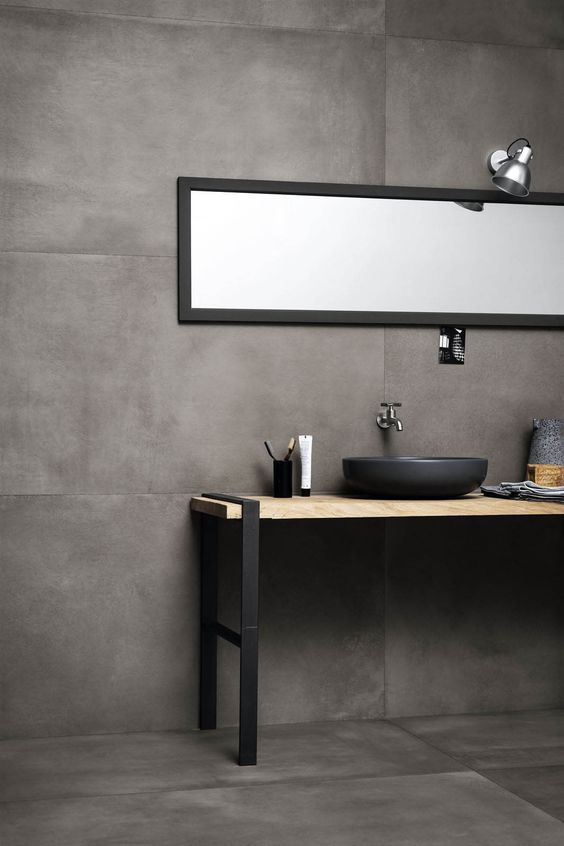 bathroom vanity with grey floor, grey wall, wooden vanity with metal legs, grey sink, long rectangular mirror, silver sconce