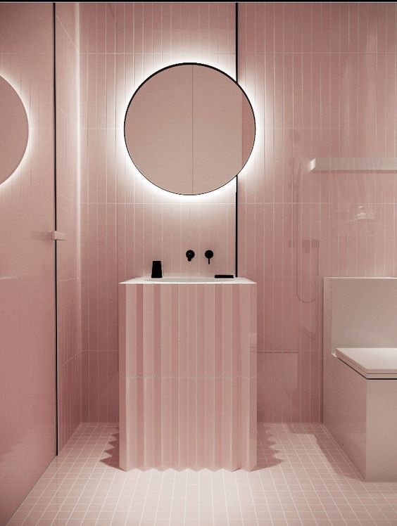 bathroom vanity with pink square tiles on floor, pink long tiles on wall, pink jagged surface sink with white sink, round mirror, white toilet
