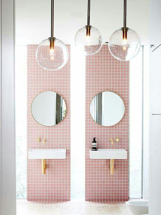bathroom vanity with white floor, double pink tiles wall support with white sink, golden pipe and faucet, round mirrors, glass pendant