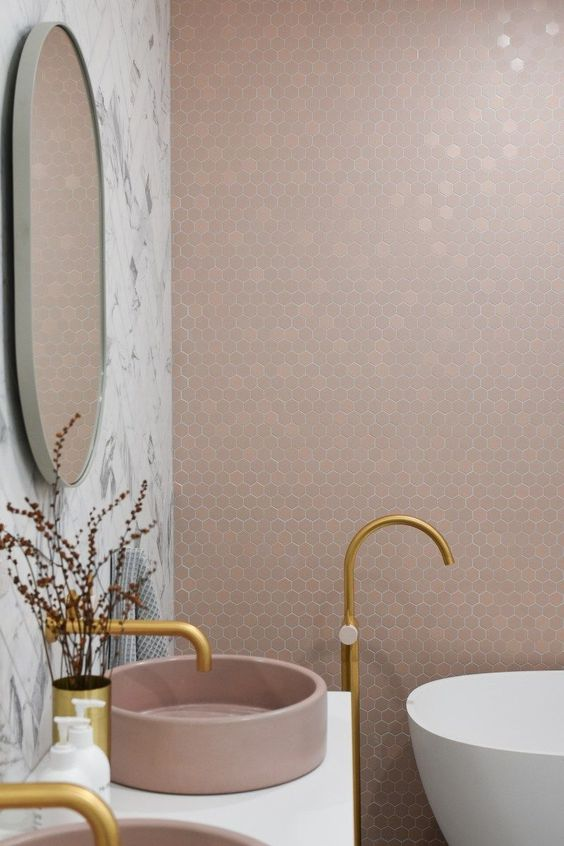 bathroom vanity with white top, pink sink, golden faucet, white marble wall, mirror, tiny pink hexagon tiles on wall